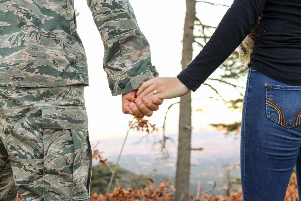 soldier holding hands with woman, no faces visible